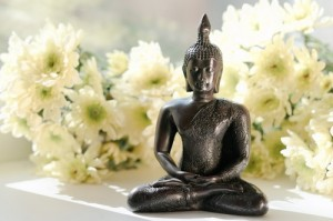 meditating buddha with white flowers
